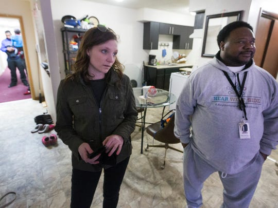 """Assistant district attorney Catelin Ringersma (left) and Safe & Sound Near West Side community prosecution unit coordinator Bobby McQuay Jr. meet with a tenant who has been having problems with her unit during a """"blight sweep"""" to take note of problems that need to be dealt with Wednesday, March 14, 2018 on the near West Side of Milwaukee, WIs. Since 2000, the Milwaukee County district attorney's office has stationed prosecutors in city neighborhoods. Each prosecutor works in tandem with a police officer and a community organizer. The teams focus on blight and take action designed to improve quality of life, such as shutting down drug houses, holding absentee landlords accountable and making sure taverns follow the rules. At its height, there were seven Community Prosecution Units, one in each police district. Now, there are three."""