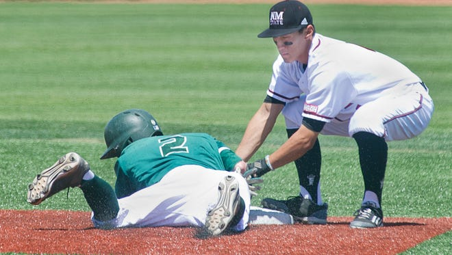 New Mexico State second basemen Brent Sakurai puts the tag on Utah Valley's Trevor Howell as Howell was trying to steal second on a bill in the dirt Sunday afternoon at Presley Askew Field.