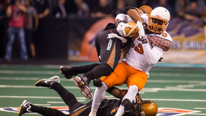 Rattlers defensive back Kerry Reed tackles Shock wide receiver Rashaad Carter during the Spokane Shock and Rattlers arena football game at US Airways on Sunday, May 18, 2014 in Phoenix.