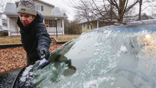 Mike Stevens, of Springfield, Mo., scrapes a thin layer of ice off of his windshield on Friday Jan. 13, 2017.