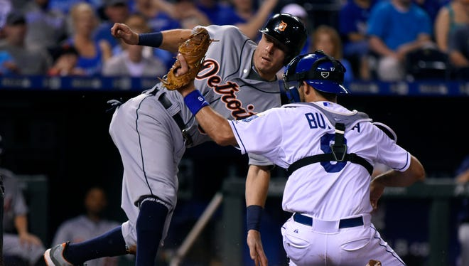 Ian Kinsler, left, of the Detroit Tigers slides past Drew Butera of the Kansas City Royals to score on a fielder's choice in the eighth inning Aug. 12, 2015, in Kansas City, Missouri.