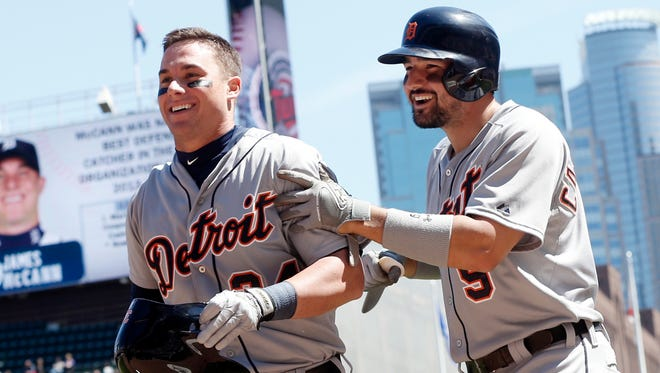 The Tigers' James McCann, left, is congratulated by Nick Castellanos after his inside-the-park home run Wednesday in Minneapolis.