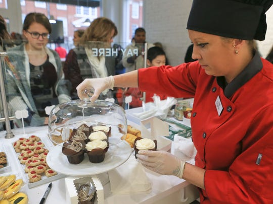 Customers Nicki Sitlinger, with daughter Kate, left, and son John, wait for their bakery goods to be ready while in line during the grand opening Jan. 16 of Scarlet's Bakery on East Oak Street in the Shelby Park neighborhood. The bakery employs disadvantaged women who may have suffered from exploitation. The neighborhood is experiencing a revitalization.
