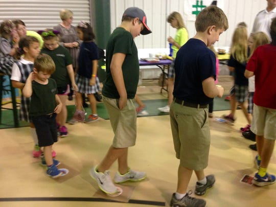 Grace Christian Schools students participate in a cake walk, stepping from papers representing different Louisiana plants as music plays Thursday.