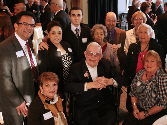 Fr. Laurence Tracy surrounded by community leaders from Rochester's Latino community in 2018.