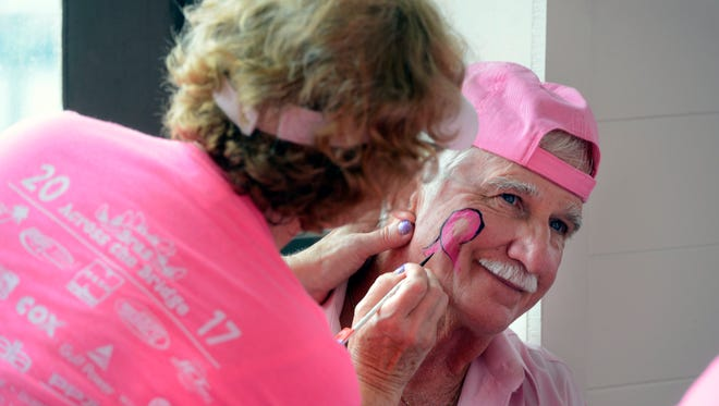 Owl Lample gets his face painted with a pink ribbon during the eighth annual Bras Across the Bridge event on Saturday, Oct. 7, 2017 at the Grand Marlin Restaurant & Oyster Bar. Breast cancer survivors, their loved ones and the community joined together to increase breast cancer awareness.