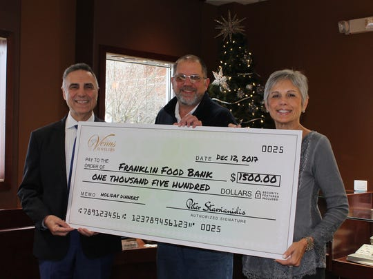 Dr. Peter Stavrianidis, the principal of Venus Jewelers, presented Frank Hasner, CEO of the Franklin Food Bank, with a check for $1,500 on Dec. 12.