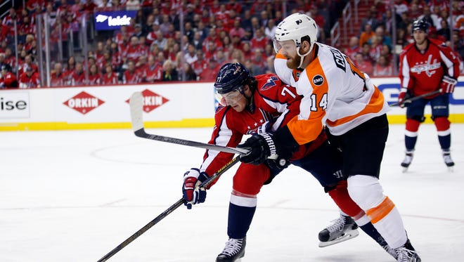 Washington Capitals right wing T.J. Oshie, left, and Flyers center Sean Couturier (14) go for the puck during the first period of Game 1 Thursday.