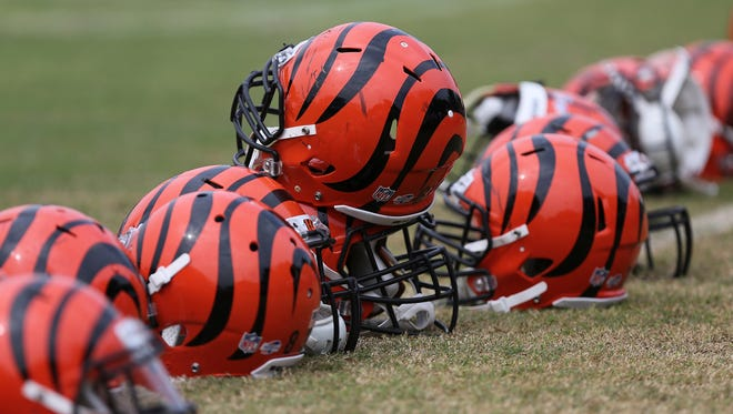 A pile of helmets sit on the sidelines during Cincinnati Bengals training camp on the practice fields adjacent Paul Brown Stadium.