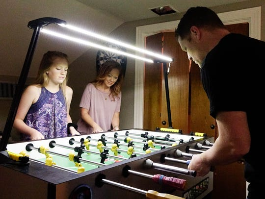 The Rue family plays foosball at home in Crowley Thurs.,