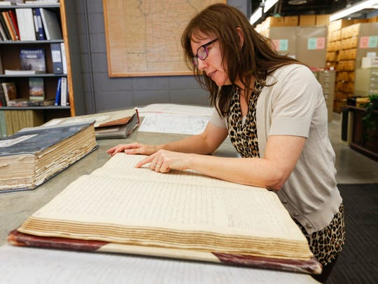 Archivist Connie Yen looks through documents while at the Greene County Archives  that tell the story of Springfield's founder inciting a riot that led to the beating of a free black woman in 1836.