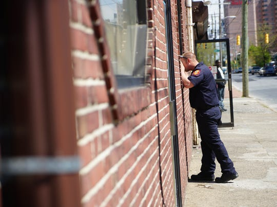 Firefighter James Johnson with the Wilmington Fire Department looks through a window of a vacant property along Washington Street.