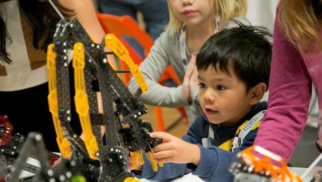 """In this Sept. 29, 2015, photo, Kenzie Nakamoto, 4, plays with toys from Hexbug at the TTPM Holiday Showcase in New York. The U.S. toy industry is expected to have its strongest year in over a decade, with anything """"Star Wars,"""" robotic and life-like pets expected to drive holiday sales."""