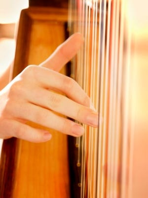 Fingers plucking on strings of a harp