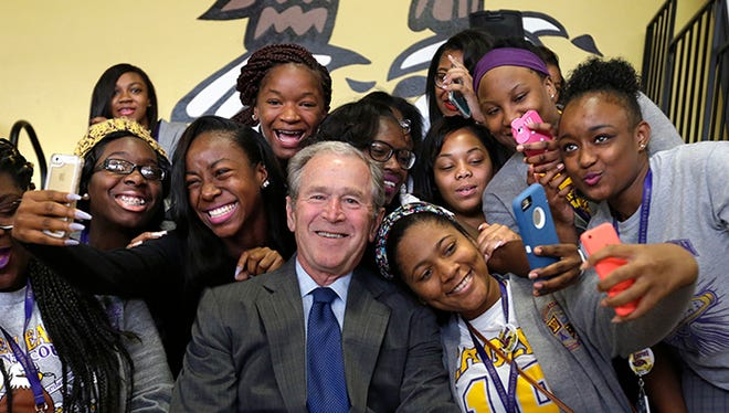 Former President George W. Bush poses for photos with students at Warren Easton Charter High School in New Orleans, Friday, Aug. 28, 2015. Bush is in town to commemorate the 10th anniversary of Hurricane Katrina, which is Saturday.