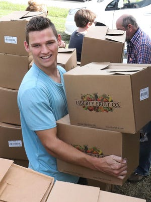 During his LDS mission trip, Elder Kahler Peterson joins other Pay it Forward - Fort Smith volunteers, Monday, Sept. 14, 2020, to distribute over 2,000 boxes of USDA GoFresh produce at the 616 N. 10th food pantry.