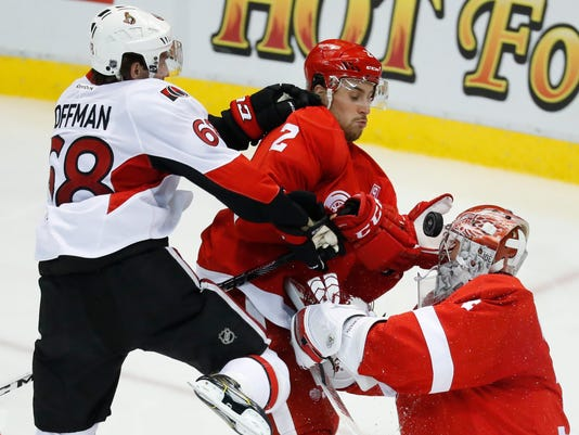 Detroit Red Wings defenseman Brendan Smith (2) knocks the puck from Ottawa Senators left wing Mike Hoffman (68) as goalie Petr Mrazek (34) defends in the third period of an NHL hockey game at Joe Louis Arena, Monday, Oct. 17, 2016 in Detroit. The Red Wings won 5-1. (AP Photo/Paul Sancya)