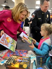 Tennessee first lady Crissy Haslam helps Cason Lane Academy second-grader Ava Molinarolo choose a book Monday, Sept. 12, 2016, as Police Chief Karl Durr passes out book markers behind her.