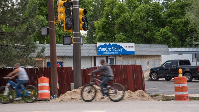 Two bicyclists leave the grounds of Poudre Valley Mobile Home Park, turning onto North College Avenue Monday, May 22, 2017. While improvements were made to the road in recent years, a 1,000-foot gap without sidewalks or bike lanes remains outside of the park's entrance.