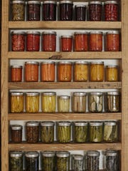 """Jars of food grown in Kate Daughdrill's urban garden are lined up for her Art X installation called """"From Here to There."""""""
