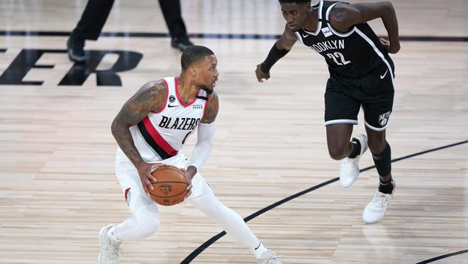 Portland Trail Blazers' Damian Lillard, left, works the floor against Brooklyn Nets' Caris LeVert during the first half of an NBA basketball game Thursday, Aug. 13, 2020 in Lake Buena Vista, Fla.