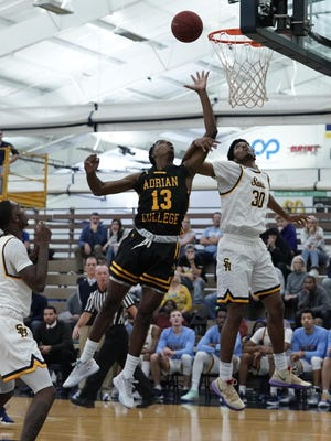 Adrian College's Kendall Bellamy (13) goes up for a rebound against Siena Heights' Keith Jordan Jr. (30) during a game on Nov. 26, 2019 at the SHU Fieldhouse.
