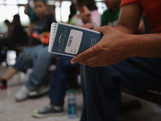 Una persona espera sentada con los boletos en la mano, antes de abordar un autobús Greyhound.