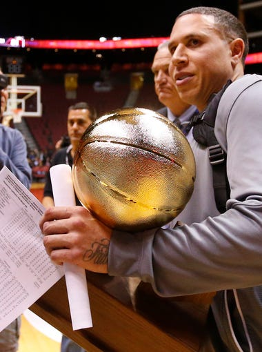 Shadow Mountain head coach Mike Bibby accepts the trophy on his team's behalf after winning the high school boys basketball 4A Conference championship on Feb. 25, 2017.
