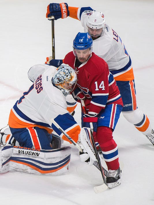 Montreal Canadiens' Tomas Plekanec (14) moves in on New York Islanders goaltender Thomas Greiss as Islanders' Nick Leddy (2) defends during the third period of an NHL hockey game Thursday, Feb. 23, 2017, in Montreal. (Graham Hughes/The Canadian Press via AP)
