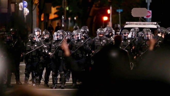 Police detain a protester on Burnside Street in Portland late Saturday.