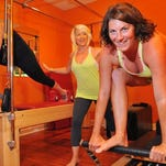 Dominique Benoit of Surabaya, Indonesia , Jessica Cassidy of Viera instructor & owner of Pilates by Jessica studio in Viera  works with Florida Today's Michelle Mulak during Thursday's Pilotes Reformer session .