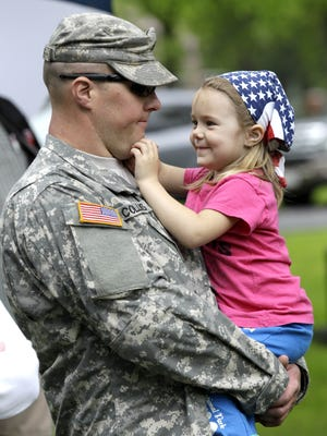 Army Sgt. Brandon Collins of De Pere shares a smile with his daughter, Katlin Heneghan, 4, during a Memorial Day ceremony Monday, May 25, 2015, at Riverside Cemetery in Appleton, Wis.