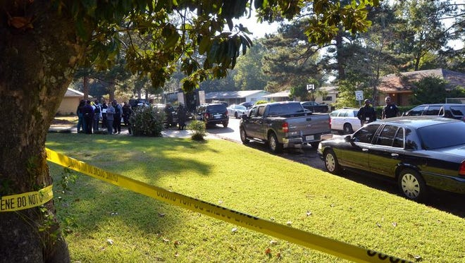 Police and SWAT team members gather outside a home in Jackson's Presidential Hills neighborhood on Monday afternoon.