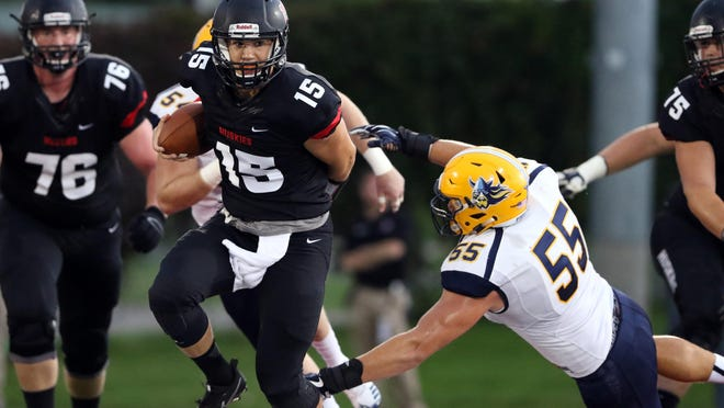 St. Cloud State quarterback Justin Czech (15) scrambles to elude the tackle of Augustana's Joey Newman (55) on Saturday at Husky Stadium.