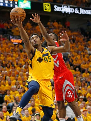Utah Jazz guard Donovan Mitchell (45) lays the ball up as Houston Rockets guard James Harden, rear, defends during the second half in Game 4 of an NBA basketball second-round playoff series Sunday, May 6, 2018, in Salt Lake City. The Rockets won 100-87. (AP Photo/Rick Bowmer)