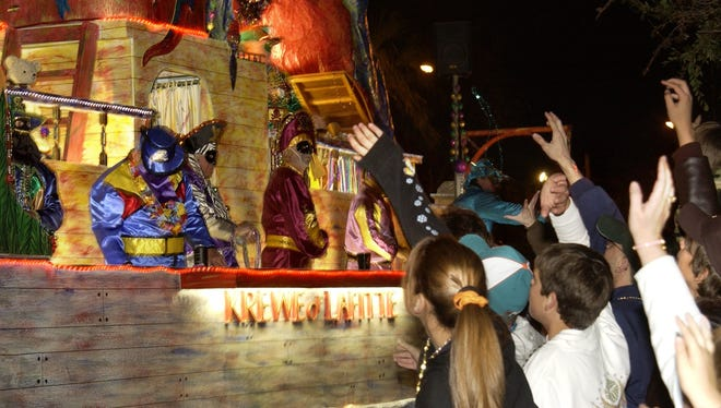 Members of the crowd try to attract the attention of the Krewe of Lafitte.