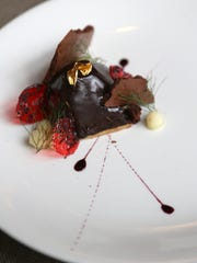 """A peanut butter mousse pyramid covered in dark chocolate ganache with candy apple and """"astronaut chocolate""""dessert from the forthcoming Chef's Table XII restaurant opening in the former Tribute restaurant space in Farmington Hills."""