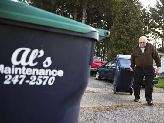 Ben Perkins rolls his garbage bins to the curb of his