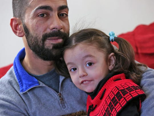 Syrian refugee Abdul Sater Khaled Assaf; his daughter,