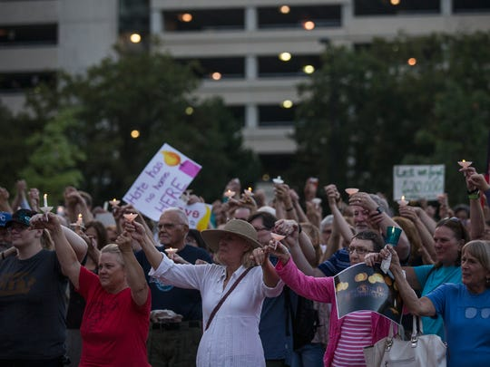 A crowd of people hold candles during a Shine the Light Against Hate Vigil hosted by the Interfaith Alliance of Iowa on Monday, Aug. 14, 2017, in Cowles Commons in downtown Des Moines.