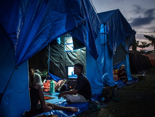 People seen inside their tent at temporary shelter
