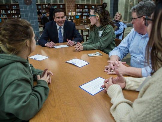 Iowa State Senator Matt McCoy talks to a family in
