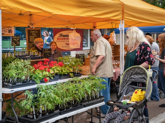 Shoppers browse at the Oshkosh Farmers Market on Main St. earlier this summer.