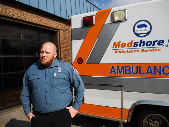 Charlie Partain, 26, a paramedic with MedShore, stands