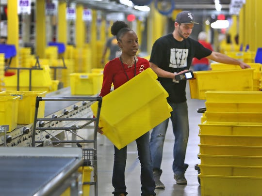 Makalah Morrissette, left, and Tim Wells fill orders in the picking area at the Amazon Whitestown Fulfillment Center on Dec. 1, 2014.