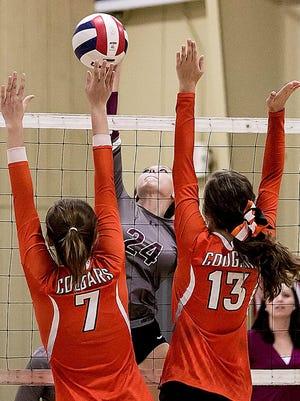 Eagleville's Hannah Cron spikes the ball against MTCS's Kalynn Kimbel (left) and Saylor Hodges.