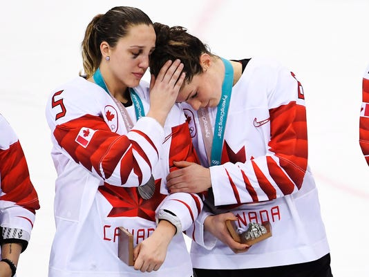 Canada's Lauriane Rougeau (5) comforts forward Rebecca Johnston (6) after losing to the United States in a shootout in the women's gold medal hockey game at the 2018 Winter Olympics in Gangneung, South Korea, Thursday, Feb. 22, 2018. (Nathan Denette/The Canadian Press via AP)