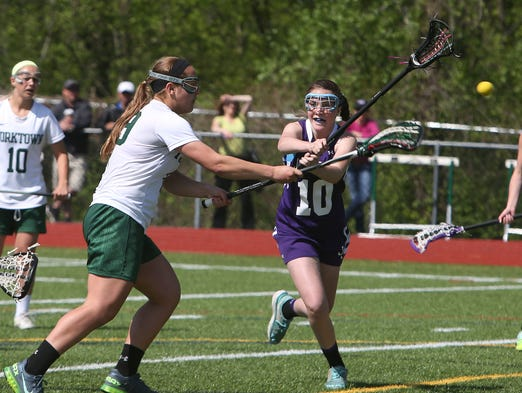 From left, Yorktown's Jenna Gammer (19) fires a shot past John Jay's Emma Gorman (10) for a first half goal during the Class B quarterfinal girls lacrosse playoff game at Yorktown High School May 17, 2014. Yorktown won the game 11-5.