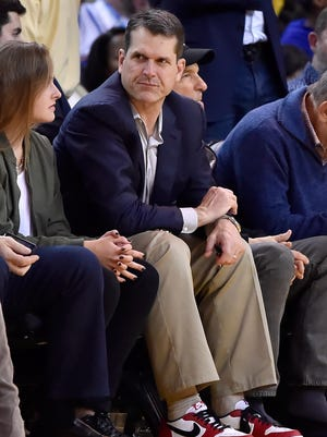 Michigan football coach Jim Harbaugh sits courtside during an NBA game between the Oklahoma City Thunder and Golden State Warriors on Feb. 6, 2016, in Oakland, California.