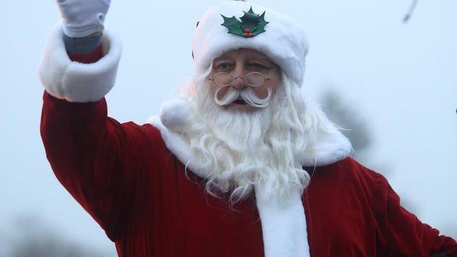 Santa Claus waves to the crowd at a past Minier Christmas parade.
